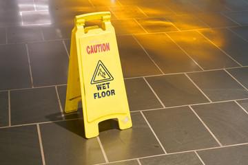 Slippery when wet warning sign in doors on the floor