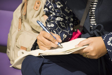 Asia traveler thai women with pen writing memorial on notebook about journey travel between waiting flight at airport