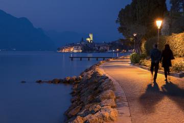 Evening walking along the shores of Garda lake, in the background  the Scaligero castle, Malcesine, Verona, Veneto, Italy