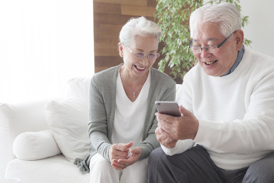 An old couple is using smartphones as they get along
