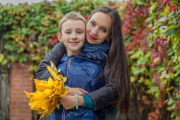 Mother and son hugging among autumn