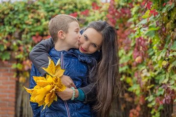Son kissing mother among autumn
