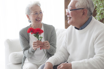 An old man who is happy to receive a flower bouquet from his wife
