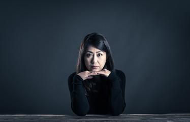 座っている女性 暗いイメージ