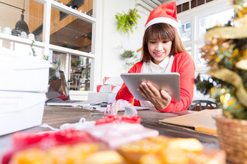 woman wearing santa hat checking order online business with teblat