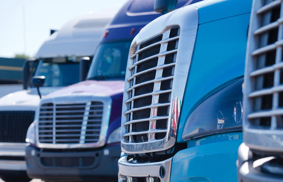 Big rig semi trucks tractors grilles in row on truck stop