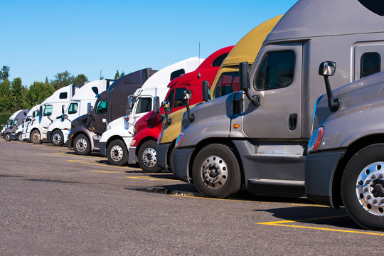 Big rigs semi trucks of different makes and models stand in row on truck stop parking lot