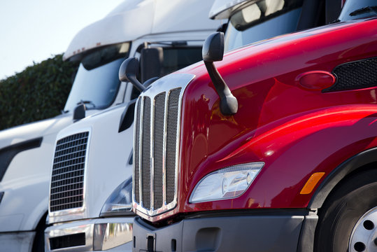 Red and white big rig semi trucks with grilles standing in line on truck stop lot
