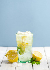 Cold lemonade and fresh lemons on a white wooden table on a blue background..