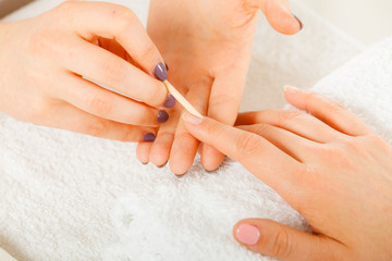 Beautician preparing nails before manicure, pushing back cuticles