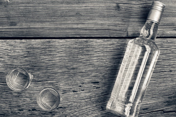 Black and white photo. VODKA luxury. Vodka in a bottle and glasses on a background of wood.