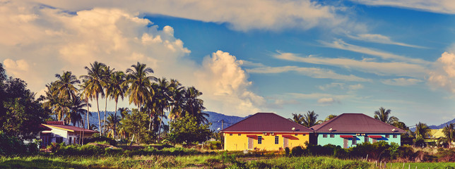 Panoramic landscape of houses surrounded by trees with background of evening sky. Colorful asian houses. Langkawi island, Malaysia. Instagram color editing.