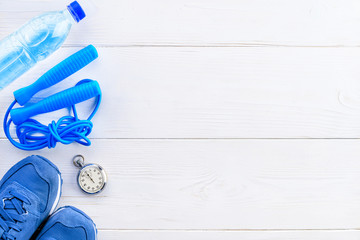 Healthy lifestyle and sport background. Sport shoes, skipping rope, stopwatch and bottle of water on the light wooden background with copyspace, top view, flat.