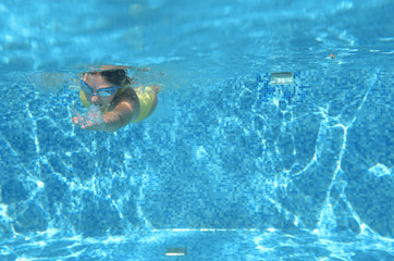 Young girl swimmer swimming under water in pool and has fun, teenager diving underwater, family vacation, sport and fitness concept