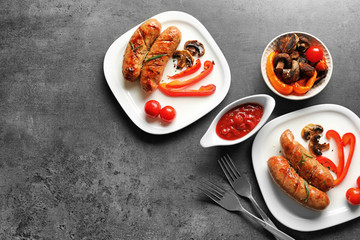 Composition with grilled sausages, vegetables and sauce on grey background