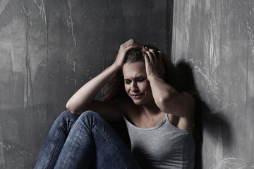 Battered sad woman sitting alone near grey wall