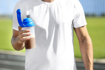 Man holding bottle with protein shake outdoors