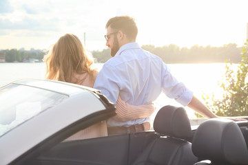 Happy young couple standing near car on river bank
