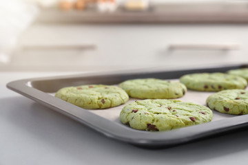 Baking tray with fresh mint chocolate chip cookies on table