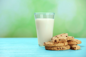 Fresh mint chocolate chip cookies and glass of milk on table