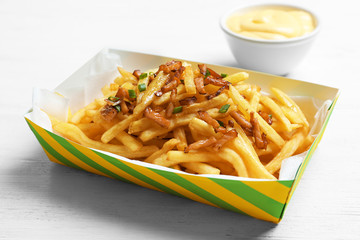 Box with french fries and bacon on table