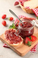 Jar and piece of bread with strawberry jam on table