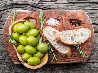 Slices of ciabatta with olives and spices on the serving wooden tray.