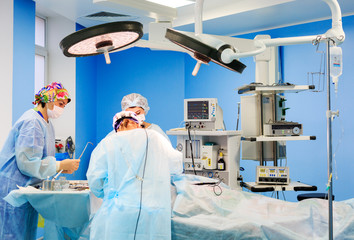 Surgeons operating a patient in operating room
