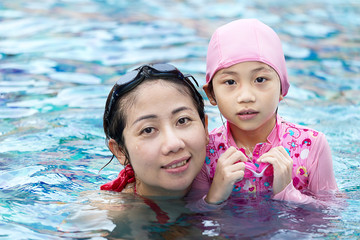 Smiling beautiful woman and little girl in a swimming pool.