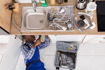 Handyman Lying On Floor Repairing Sink
