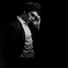 Thinking depression charismatic man looking down on dark shadow dramatic light background. Closeup black and white portrait. Art