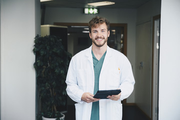 Portrait of confident smiling male doctor standing with digital tablet at hospital corridor