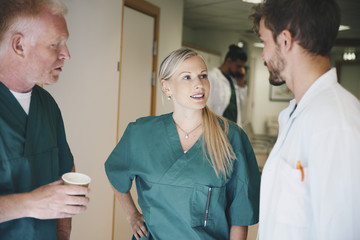 Medical colleagues discussing while standing in corridor at hospital