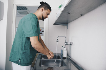 Side view of male nurse washing hands in sink at hospital