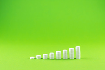 Close up pyramid concept of white pills on green background with copy space. Focus on foreground, soft bokeh. Pharmacy drugstore concept