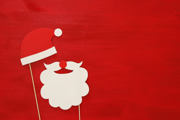 Christmas concept top view image. Santa claus beard and hat on red wooden background