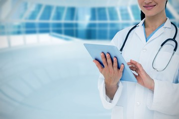 Composite image of happy doctor using her tablet pc