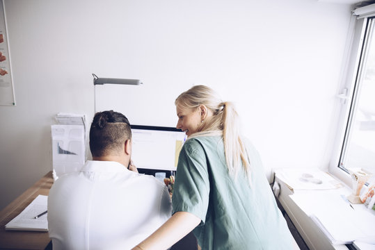 Rear view of female nurse and male doctor discussing at office in hospital