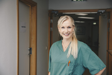 Portrait of confident female nurse standing in hospital corridor
