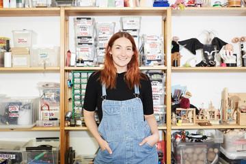 Portrait of confident redhead female technician standing against shelf at workshop