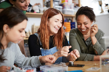 Cheerful female engineers working at table in workshop