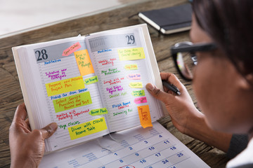 Fototapete - Businesswoman Looking At List Of Business Work In Diary