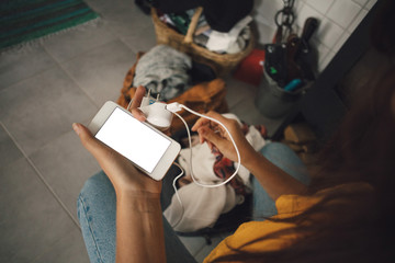 Midsection of young woman holding mobile phone and charger at home