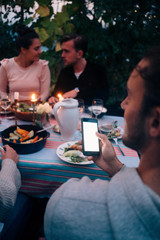 Young man holding mobile phone while friends communicating at dining table