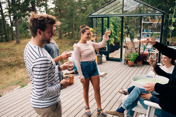 Happy male and female friends raising toast on cottage deck