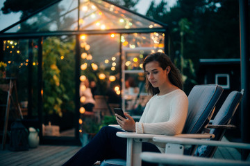 Young woman using mobile phone while sitting on lounge chair against glass cabin