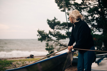 Young woman tying boat at beach