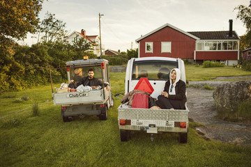 Young friends sitting in vehicles against house