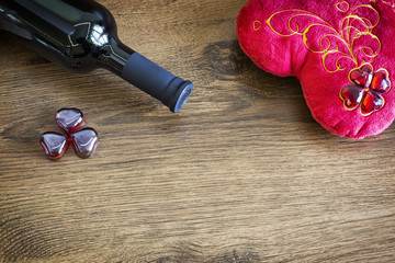 Valentines day background. A bottle of red wine, big, red, valentines heart on wooden background
