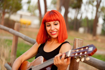 Red hair woman playing guitar